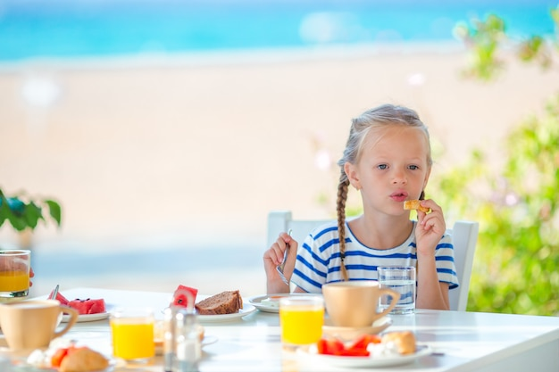 Adorable little girl having breakfast at cafe with sea view early in the morning Premium Photo