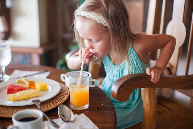 Adorable little girl having breakfast and drinking fruit cocktail Premium Photo