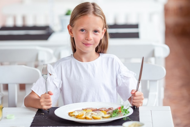 Adorable little girl having dinner at outdoor cafe Premium Photo