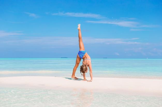 Adorable little girl having fun making cartwheel on tropical white sandy beach Premium Photo