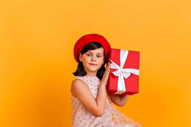 Прелестная маленькая девочка в платье, держащем подарок на день рождения. ребенок гадал, что в подарок. Бесплатные Фотографии
