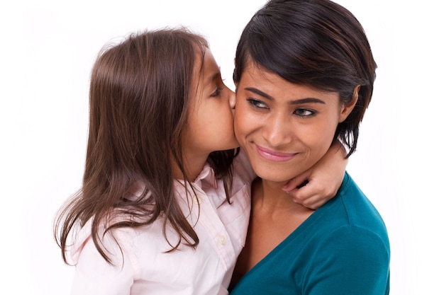 Adorable little girl kissing her mother's cheek Premium Photo