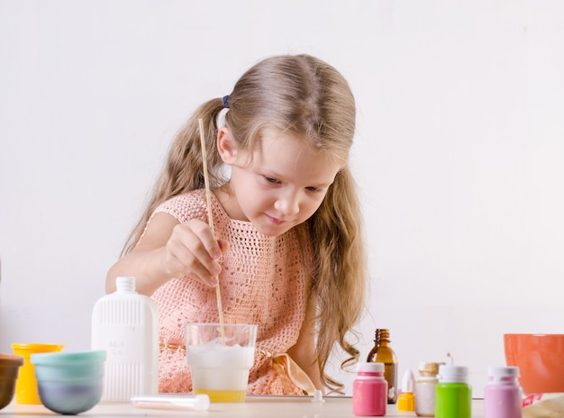Adorable little girl making slime toy, meshes ingredients for worldwide popular self made toy. Premium Photo