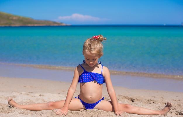 Adorable little girl making wheel on tropical white sandy beach Premium Photo