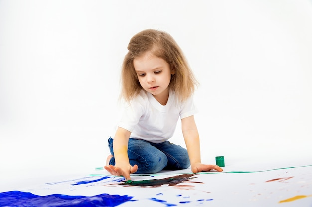Adorable little girl, modern hair style, white shirt, blue jeans is drawing pictures by her hands with paints. isolate. Premium Photo