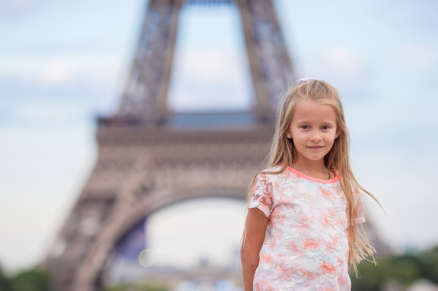 Adorable little girl in paris background the eiffel tower during summer vacation Premium Photo