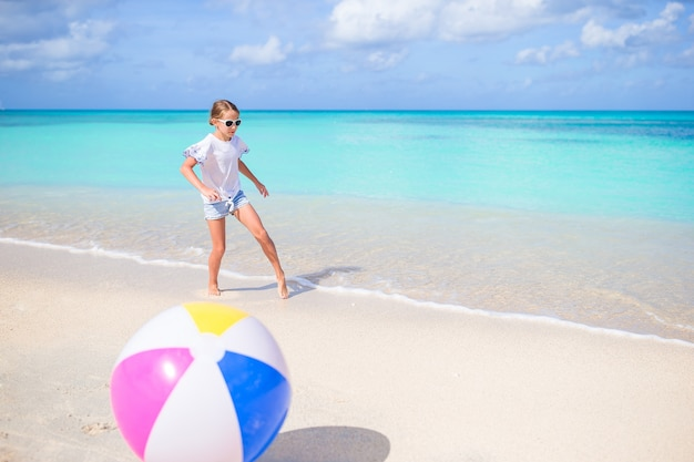 Adorable little girl playing with ball on beach, kids summer sport outdoors Premium Photo