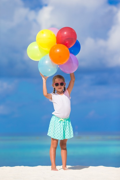 Adorable little girl playing with balloons at the beach Premium Photo