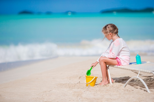 Adorable little girl playing with toys on beach vacation. kid play with sand Premium Photo