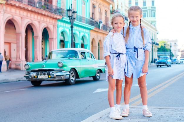 Adorable little girl in popular area in old havana, cuba. portrait of two kids outdoors on a street of havana Premium Photo