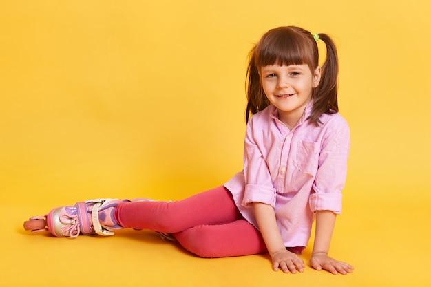 床に座っているかわいい女の子。 無料写真