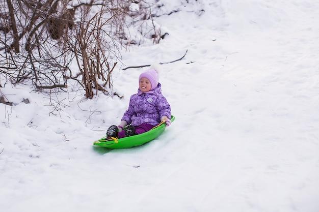 Adorable little girl sledding in snowy forest Premium Photo