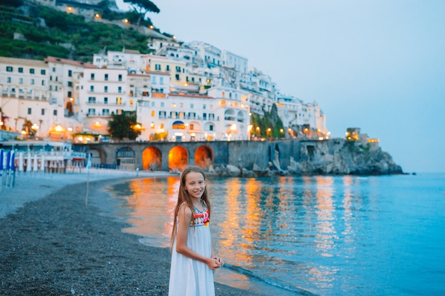 Adorable little girl on sunset in amalfi town in italy Premium Photo
