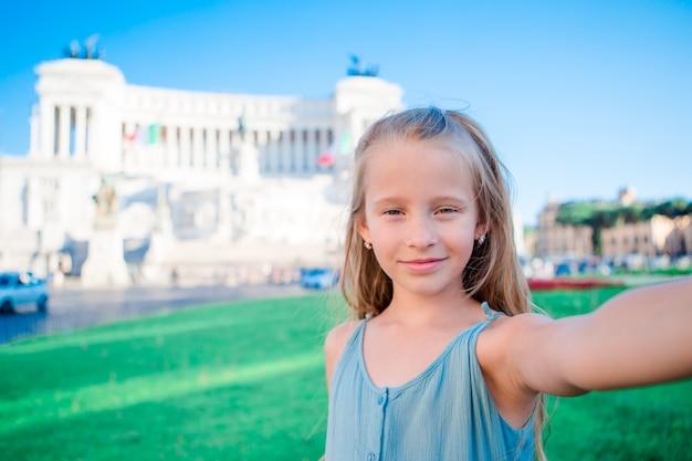 Adorable little girl taking selfie in front of altare della patria, monumento nazionale a vittorio emanuele ii also known as ii vittoriano, rome, italy. Premium Photo
