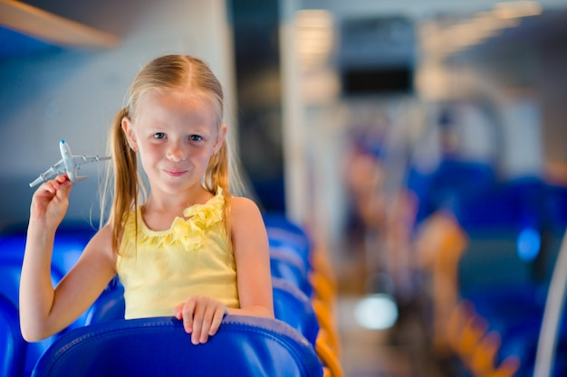 Adorable little girl traveling on train and having fun with airplane model in hands Premium Photo
