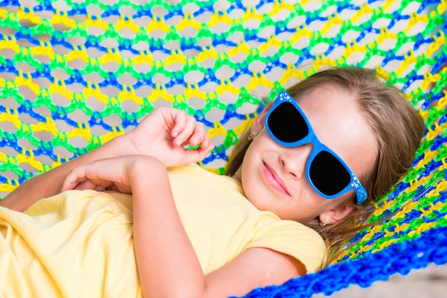 Adorable little girl on tropical vacation relaxing in hammock Premium Photo
