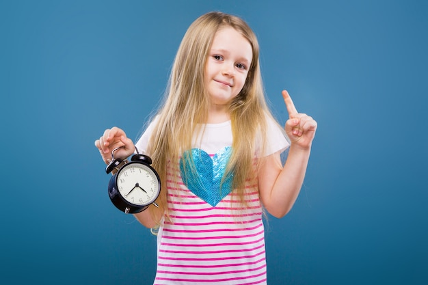 Adorable little girl in white striped shirt with blue heart and jeans hold alarm clock Premium Photo