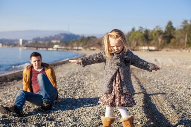 Adorable little girl with father having fun on beach in winter warm day Premium Photo