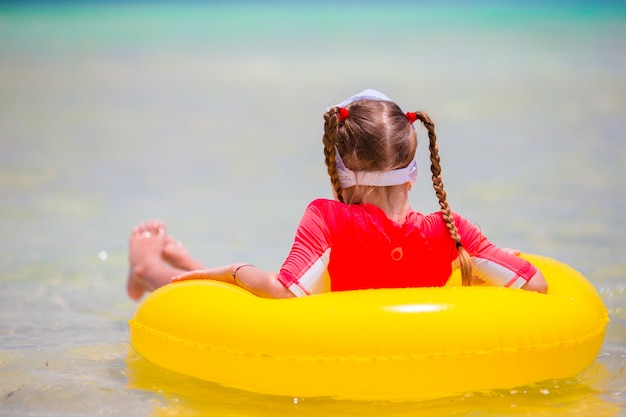 Adorable little girl with inflatable rubber circle during beach vacation. kid having fun on summer active vacation Premium Photo