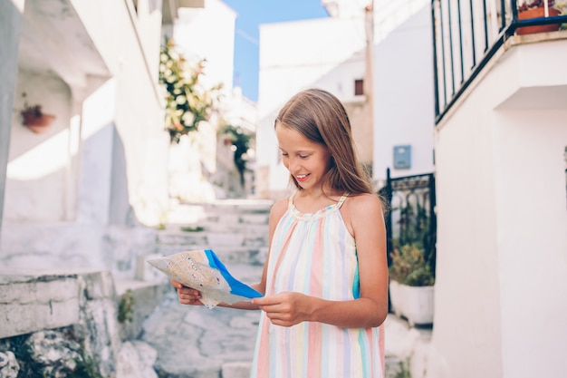 Adorable little girl with map of european city outdoors Premium Photo