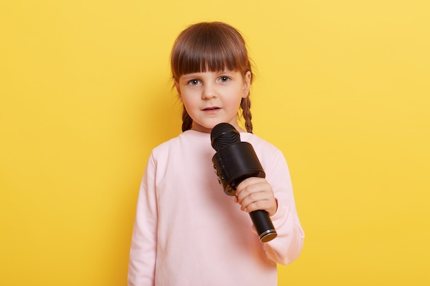 Adorable little girl with microphone on yellow background, looks at camera while talking in mic, pointing index finger aside. copy pace for advertisement or promotional text. Free Photo