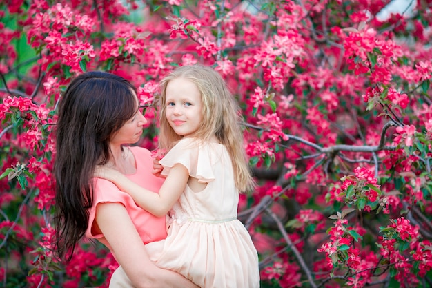 Adorable little girl with young mother in blooming cherry garden on spring day Premium Photo