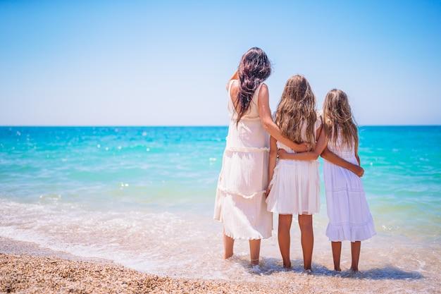 愛らしい少女と熱帯白いビーチで若い母親 Premium写真