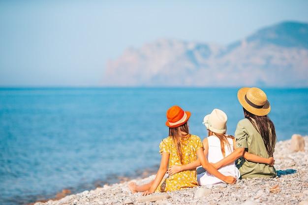 Очаровательные маленькие девочки и молодая мать на тропическом белом пляже Premium Фотографии