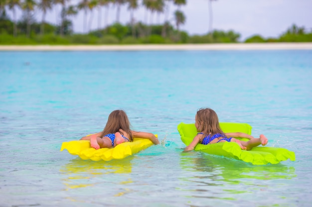 Adorable little girls on inflatable mattress in the sea during summer vacation Premium Photo