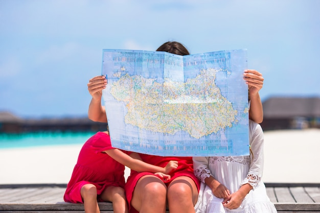Adorable little girls and mom with map of island on beach Premium Photo