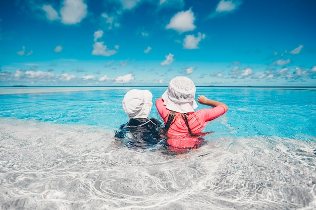 Adorable little girls playing in outdoor swimming pool on vacation Premium Photo