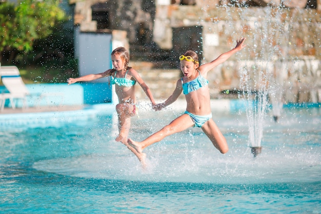 Adorable little girls playing in outdoor swimming pool Premium Photo