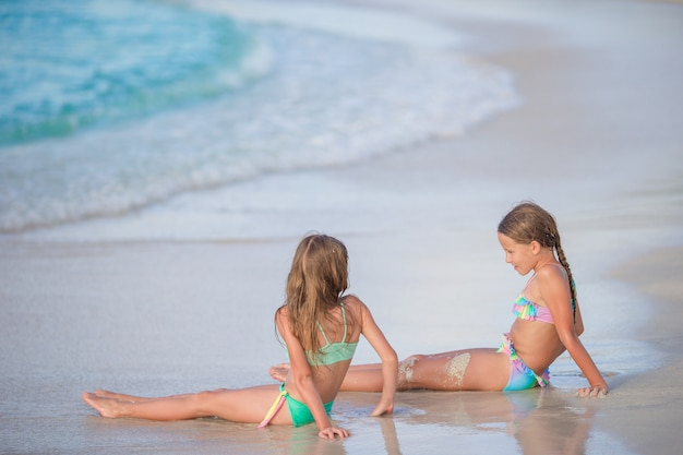 Adorable little girls relaxing on the beach Premium Photo