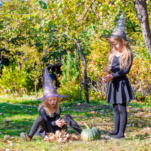 Adorable little girls in witch costume on halloween outdoors Premium Photo