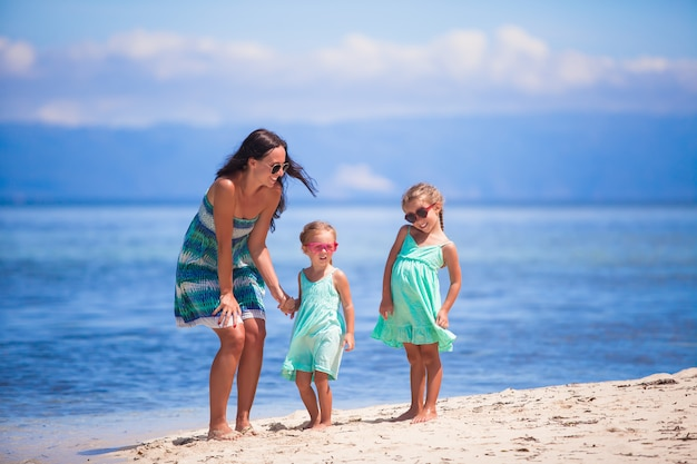 Adorable little girls and young mother have fun on tropical white beach in desert island Premium Photo