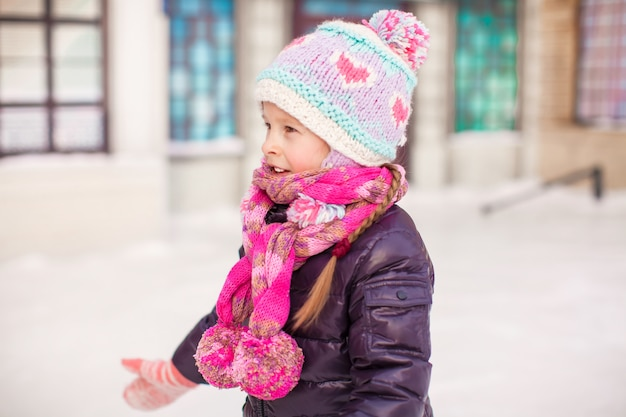 Adorable little happy girl skating on the ice-rink Premium Photo