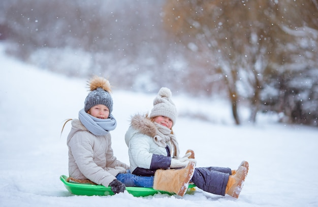 Adorable little happy girls sledding in winter snowy day. Premium Photo