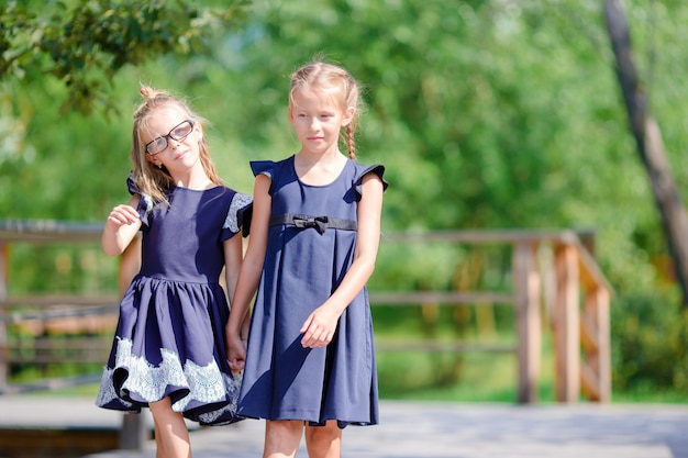 Adorable little school girls outdoors in fall Premium Photo