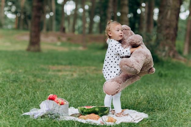 晴れた日に夏の公園で楽しんでいる大きなテディベアと愛らしい小さな幼児の女の子。夏の休日のピクニックのコンセプトです。セレクティブフォーカス。 Premium写真