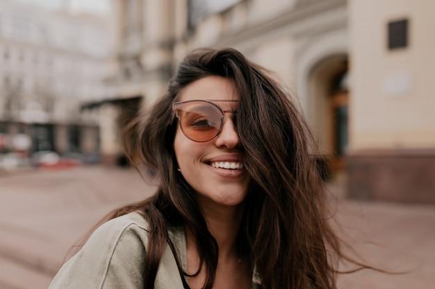 通りを歩きながら屋外のカメラでポーズをとってファッションメガネをかけて黒髪の愛らしい素敵な女性 無料写真