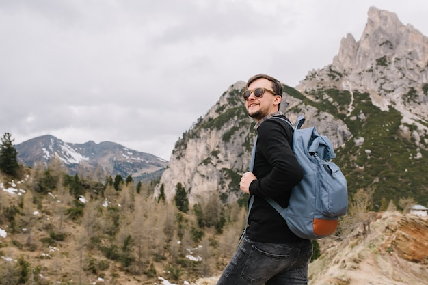 Adorable man wearing sunglasses climbing in mountains and looking away, holding blue backpack Free Photo