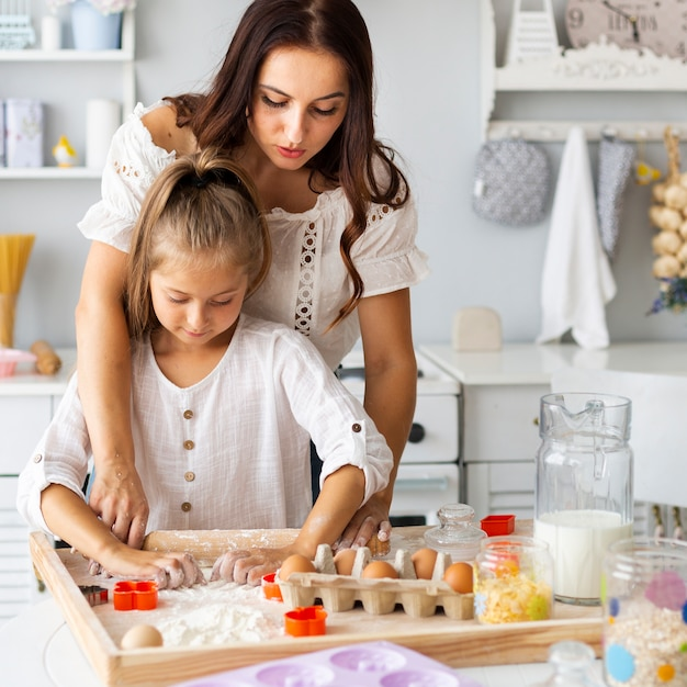 Adorable mother and daughter preparing cookies Free Photo