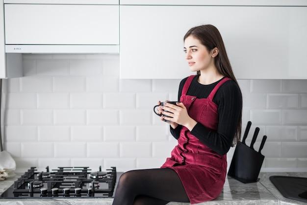 Очаровательная милая очаровательная девушка пьет кофе, сидя на столешнице стола в современной светло-белой кухне Бесплатные Фотографии