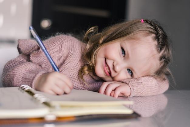 테이블에 펜으로 그리는 사랑스러운 유치원 소녀 무료 사진