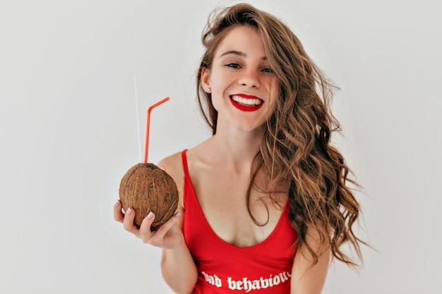 赤い口紅と長い薄茶色の髪の愛らしいきれいな女性は、ココナッツと赤い水着を着ています 無料写真