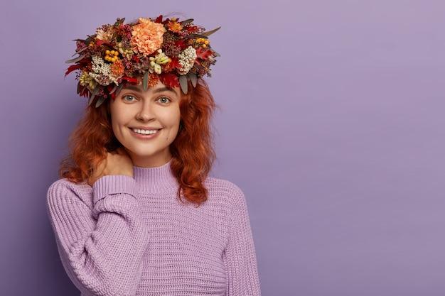 사랑스러운 빨간 머리 여자는 부드러운 미소를 가지고 있으며, 목, 건강한 피부를 만지고, 수제 가을 화환, 니트 보라색 점퍼를 착용하고 빈 공간이있는 보라색 벽에 서 있습니다. 무료 사진