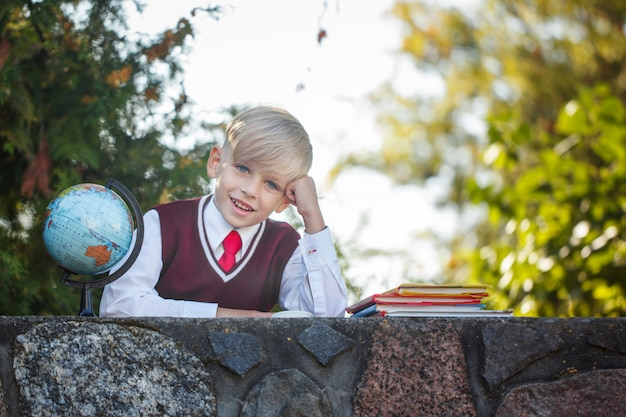 Adorable schoolboy with books and globe on outdoors. education for kids. back to school concept. Premium Photo