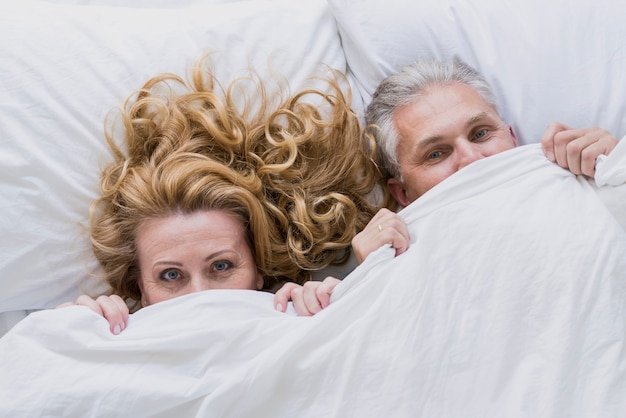 Adorable senior couple under bed sheets Free Photo