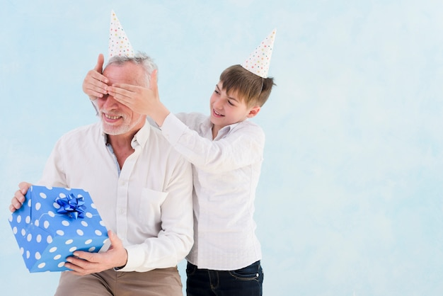 Adorable smiling boy giving surprised gift to his grandfather by covering his eyes against blue background Free Photo