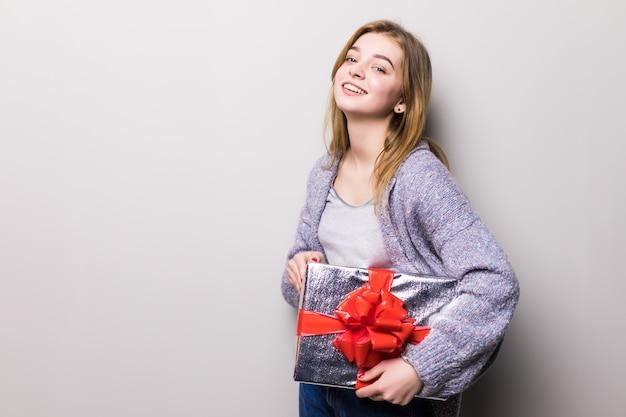 Очаровательная девочка-подросток смотрит на коробку с подарком, изолированную на белом Бесплатные Фотографии